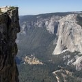 The promintory of Taft Point juts out into space, 3,500 feet above the valley floor. The monolith of El Capitan stands proudly in the background.- Taft Point