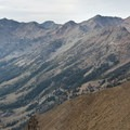 A view looking up the entire North Fork of the Big Wood Canyon from Ibex Peak. The trail stays on the right side of the canyon through the many open avalanche-swept meadows. The limestone gorge and waterfall is in the lower left side of the photo.- North Fork of the Big Wood