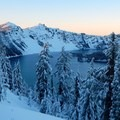The sun sets over Crater Lake.- The Watchman Snowshoe