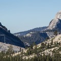 The Lone Boulder, a key landmark for route-finding, sits on the ridge beyond the first forested valley.- Tenaya Canyon Descent