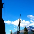 A climber is silhouetted on the left as a peak looms in the distance.- Edge of Time