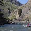 A trio of boats floats past tilted layers of metamorphic gneiss.- Middle Fork of the Salmon River - Day 6
