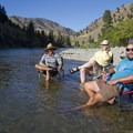 River guides and non-hiking guests relax on the gravel bar at Big Loon Camp.- Middle Fork of the Salmon River Trail – Day 4