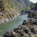 After the maelstrom of Blossom Bar, the river settles down and slips placidly past bedrock walls.- Rogue River Trail – Day 3