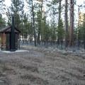Thompson Reservoir Campground vault toilet facility.- Thompson Reservoir Campground