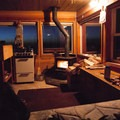 There are three beds, a wood stove, and a small kitchen area.- Hager Mountain Fire Lookout