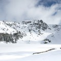 Frozen Emigrant Lake at the bottom of a mountain bowl.- Emigrant Lake Trail