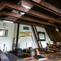 Main room with woodburning stove and a ladder to the loft sleeping area.- Ludlow Hut