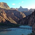 Early morning east-facing view from the south bank of the Colorado River. Silver Bridge visible in the foreground, Black Bridge in the background. Sumner Butte and Zoroaster Templer tower above.- South Kaibab + Bright Angel Trails