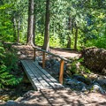 A bridge leads between sites at the Chatter Creek Campground.- Chatter Creek Campground