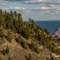The Grand Canyon Lodge, North Rim, peaks out from the pines as the canyon opens up beneath.- Transept Trail