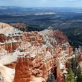 The trail peers down on the tops of rocky spires.- Under-the-Rim Trail to Hat Point