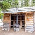 A three-walled hut with a wood burning stove for cold weather camping.- Aneroid Lake
