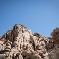 A climber scrambles to the top of a rockpile.- Hidden Valley Nature Trail