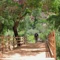Crossing a bridge over Havasu Creek.- Havasu Falls Hike via Havasupai Trail