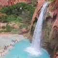 Havasu Falls is a 90-foot to 100-foot vertical waterfall that goes over a cliff into a large pool.- Havasu Falls Hike via Havasupai Trail