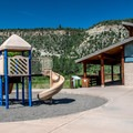 Camper services building, including laundry and showers, and the playground. - Pa-Co-Chu-Puk Campground