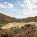Tailings piles from past mining activity remain present throughout the hills and immediately beside the trail.- Evans Canyon/Miner's Trail Loop