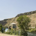 Diversion Dam in the distance with water cascading over the edge of the dam.- Boise River Greenbelt