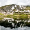 The lake has a beautiful backdrop of late season snow patches.- Ptarmigan Lake Trail