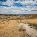 The concrete directional arrow pointing eastward atop the hill.- Steamboat Ditch Trail