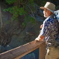 A JMT hiker enjoying the view at one of the many bridges along the Mist Trail.- John Muir Trail Section 1
