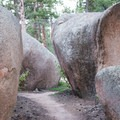 Squeezing through boulders towards the trail's end.- Little Scraggy Mountain Bike Ride