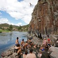A cliff jumper leaps off the rock as a crowd looks on.- Radium Hot Springs
