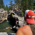 A woman watches cliff jumpers at Devils Punchbowl. - Devils Punchbowl Swimming Hole