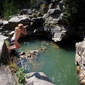 A cliff jumper takes the plunge into Devils Punchbowl.- Devils Punchbowl Swimming Hole