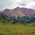 Backpackers descend from Buckskin Pass with the Maroon Bells in the distance. - Four Pass Loop