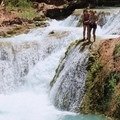 A hiker prepares to jump into the cool waters below. - Mooney + Beaver Falls Hike from Supai