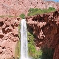 After climbing with footholds, chains, and rock ledges, Mooney Falls is visible from the landing.- Mooney + Beaver Falls Hike from Supai