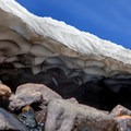 Snow caves form under the melting snow (very dangerous to enter).- Saint Mary's Glacier + Saint Mary's Lake