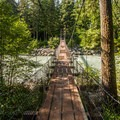 A suspension bridge over Callaghan Creek from the South Loop leads to Lava Lake and Brandywine Falls.- Cal-Cheak Recreation Site + Campground