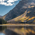 Light plays on the shoulders of the Maroon Bells near Crater Lake.- Crater Lake + Maroon Lake Hike via the Maroon-Snowmass Trail
