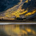 Sunlight on the aspens at Crater Lake in Colorado's Maroon Bells-Snowmass Wilderness.- Crater Lake + Maroon Lake Hike via the Maroon-Snowmass Trail