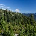 Hidden mountains come into view from the backside of the mountain.- Mount Seymour Summit Hike