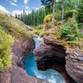 Turquoise water contrasts against the red riverbed rock and yellow leaves.- South Fork Mineral Creek