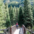 The path first crosses a bridge over the Roaring Fork River- The Grottos Hiking Trails