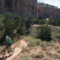 The trail skirts the red rock cliffs that rise over 100 feet overhead.- Kokopelli Loops Mountain Bike Trails: Horsethief Bench