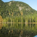 The cabin is virtually unseen from the opposite side of the lake.- Elsay Lake Hiking Trail