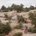 Climbing slickrock.- Gooseberry Mesa Mountain Biking: South Rim, Hidden Canyon + White Trail