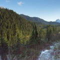 The park's peaks come into view passing Victors Landing.- Mount Steele Hike
