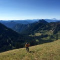 A hiker making his way up the meadow while Mount Adams resides on the horizon.- Tamanos Mountain Hike