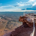 Sturdy guardrails protect the cliff's edge.- Needles Overlook