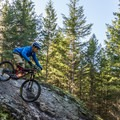 Riding a rock feature on Out There.- North Whistler Mountain Bike Trails: Out There