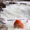 A paddler emerges from Oh, By The Way with the Ledges in the background.- New Haven Ledges