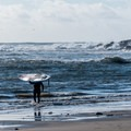 A paddleboarder heads out to surf at Mavericks.- Mavericks Beach