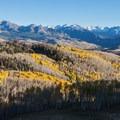 Ragged mountains behind aspen along Last Dollar Road.- Last Dollar Road